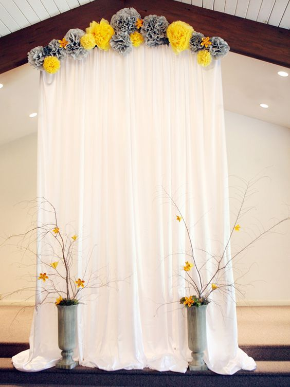 tissue pompom wedding arch and paper yellow flowers