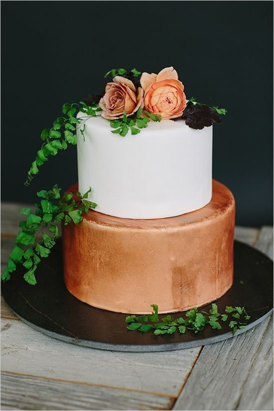 copper and white wedding cake topped with greenery and flowers