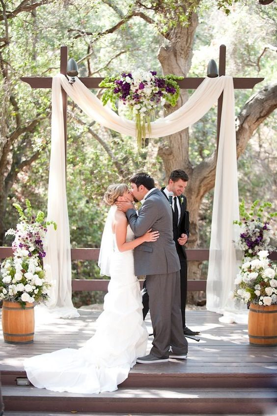 wooden arch with white fabric and moody flowers