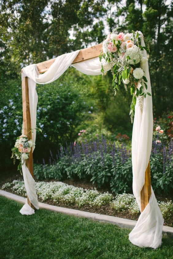 wooden arch with white fabric and pastel flowers