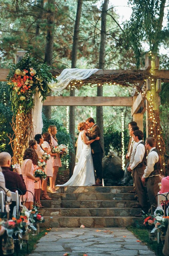 wooden wedding arbor decorated with draped fabric, lush florals and lights