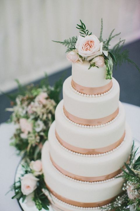 five-tiered wedding cake with copper ribbon and fresh flowers