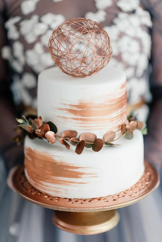 simple, chic, white cake with a modern make-over, brushed with copper strokes and adorned with copper sprayed eucalyptus