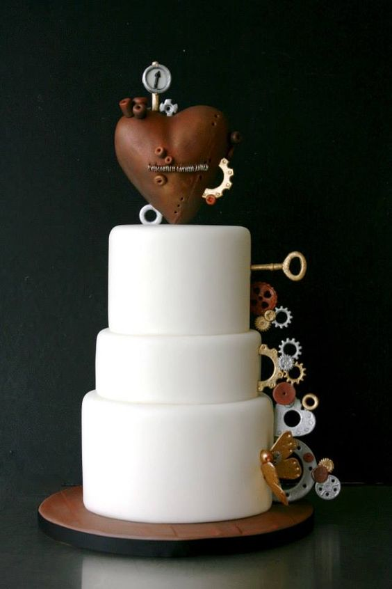 plain white wedding cake decorated with gears, a large heart and keys