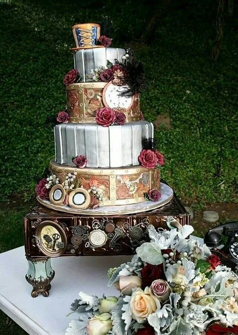 steampunk wedding cake with red flowers and a hat on top