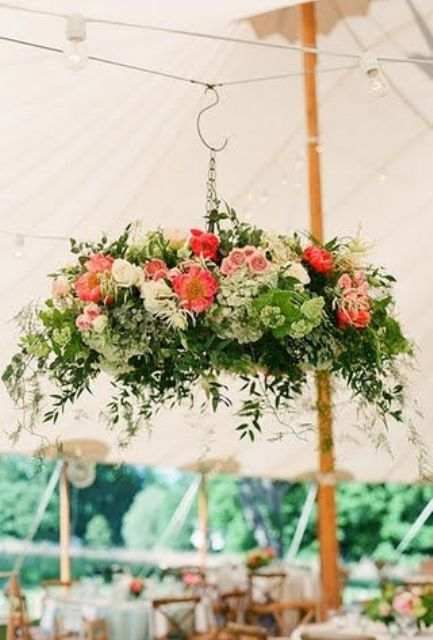 awesome flower and greenery chandelier on a hook above the tented reception