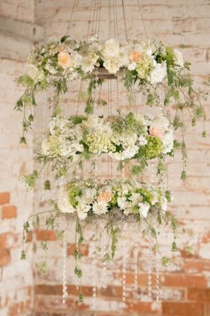 three tier whimsical hanging floral chadelier that consists of blush, ivory, and green blooms