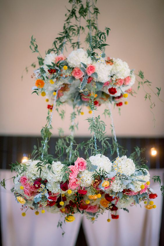 Elegant two tier floral chandelier with bold colors and greenery can fir a boho wedding
