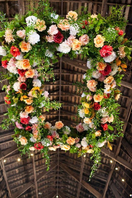 vibrant floral chandelier with greenery and leaves for a barn wedding