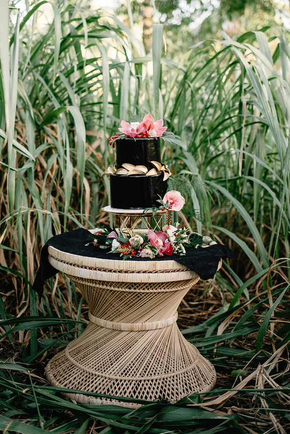 The black wedding cake was topped with tropical flowers and leaves, it gave a moody feel to the shoot