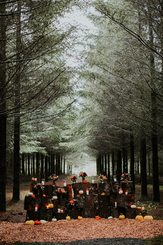 The ceremony backdrop was made of wood logs, candles in candleholders and bold fall flowers were placed right on them