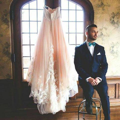 a navy and white lace applique bridal dress and a groom in a navy suit