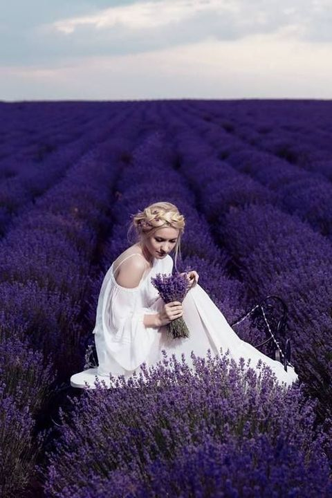 bride in a cold shoulder wedding dress with a lavender crown and bouquet in a lavender field