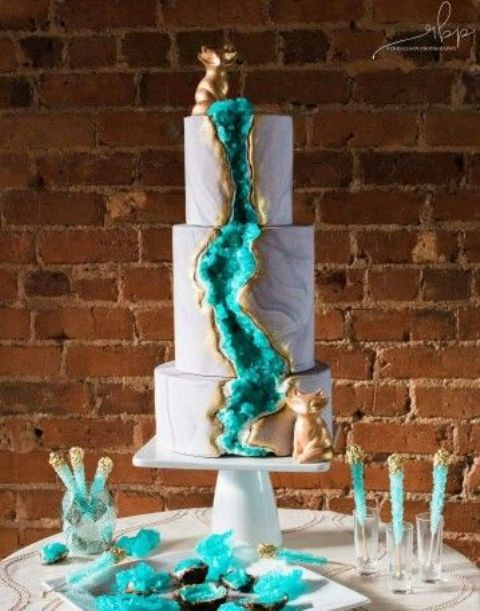 stunning turquoise geode wedding cake with gold rim and animal toppers