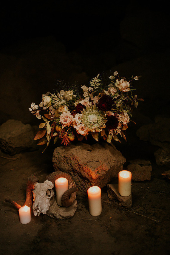 Artificial skulls, candles and moody florals created a mood for the shoot