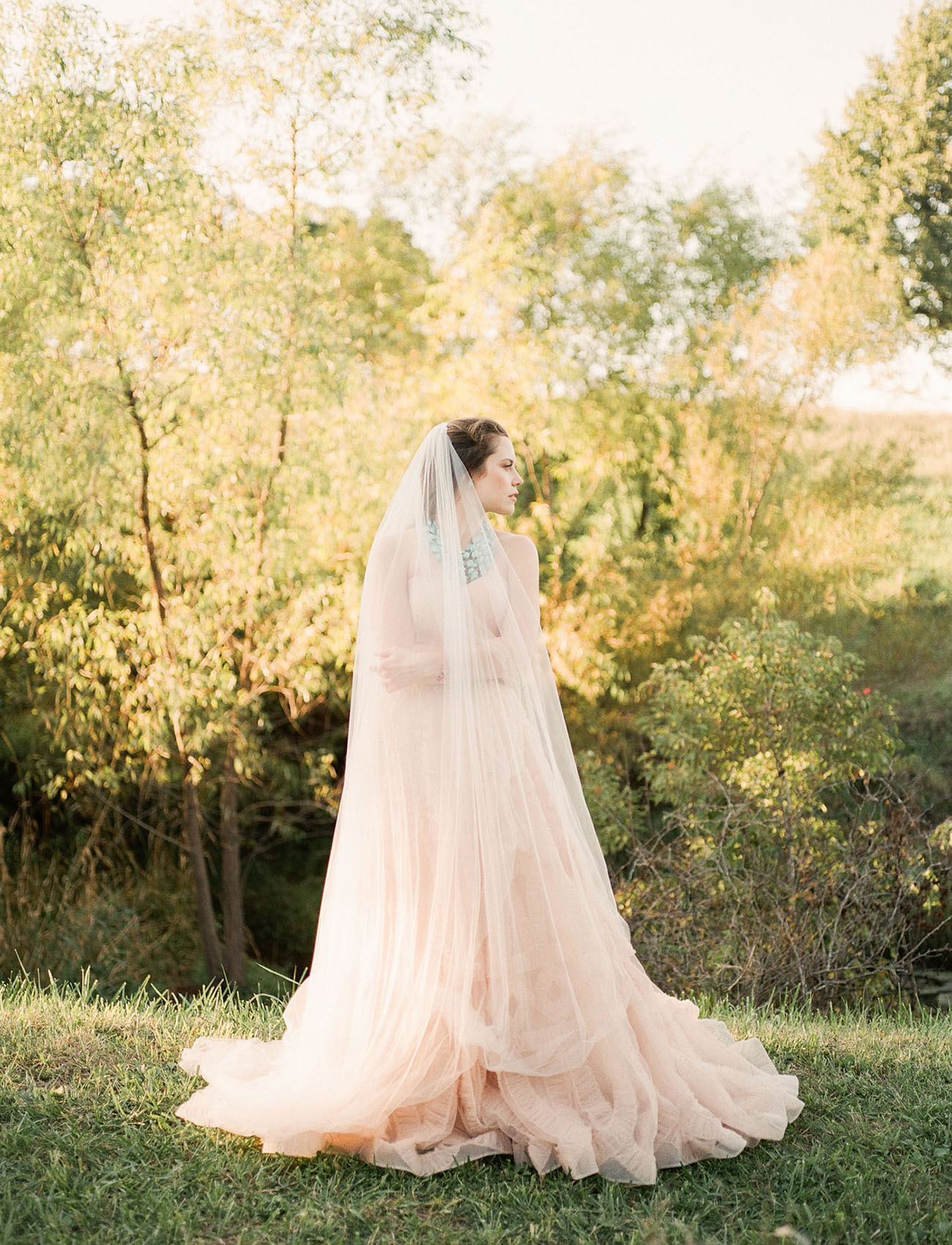 The bride was wearing a gorgeous wedding gown in blush and a matching veil, both with texture