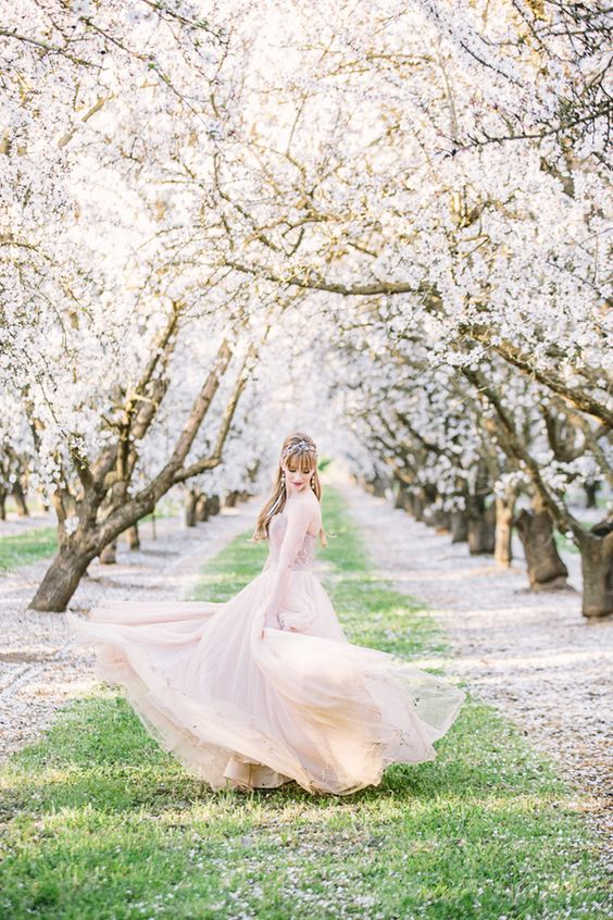 a beautiful blush wedding dress echoes with the blush trees around