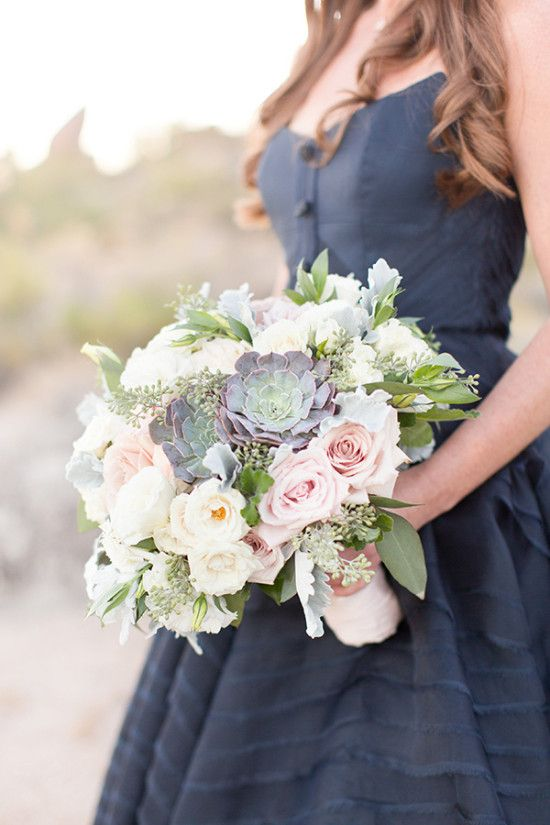 a navy bridesmaid's dress with ivory and blush bouquet