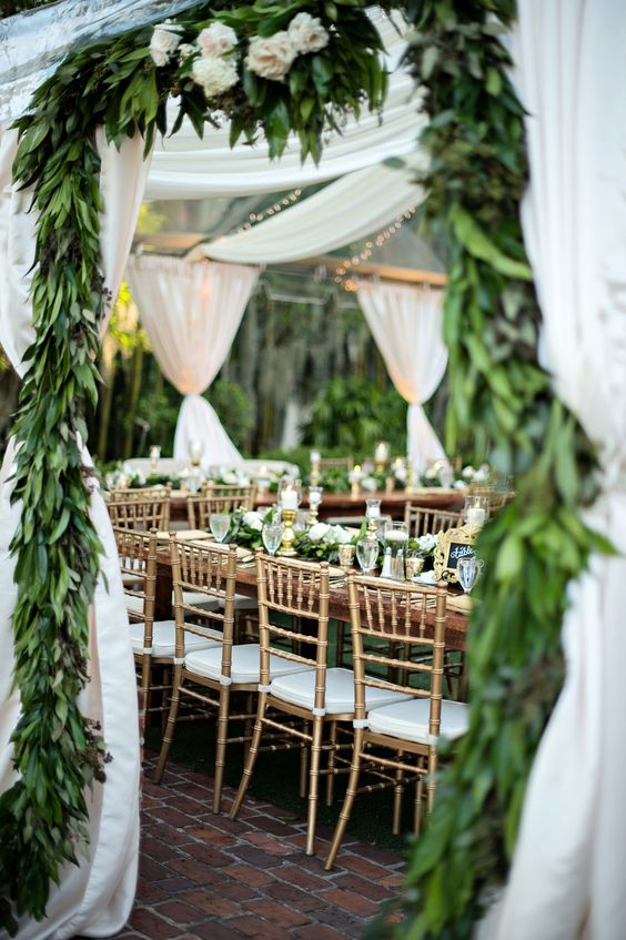 a wedding tent with greenery garlands all over
