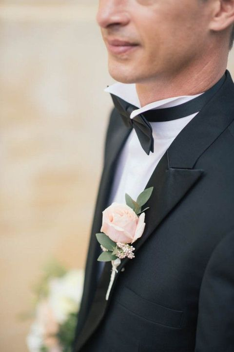 a black tuxedo with a blush rose boutonniere