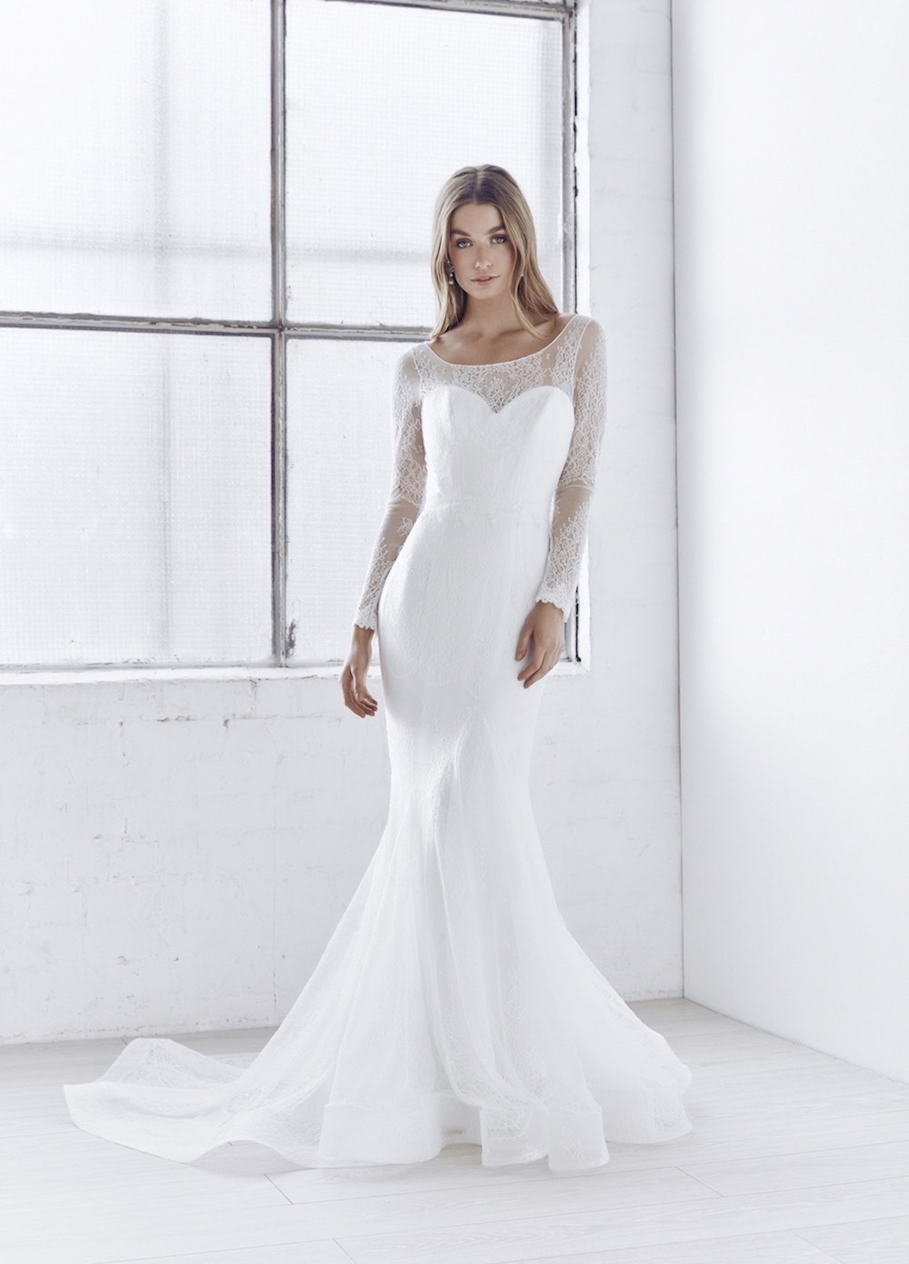 With an elegant illusion neckline, long sleeves, and fitted trumpet skirt in delicate ivory lace, the soft, ethereal elegance of the Milla Dress is both sexy and sweet