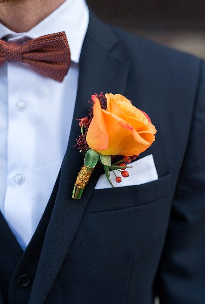 the groom rocked a black suti with a copper-colored bow tie and an orange rose