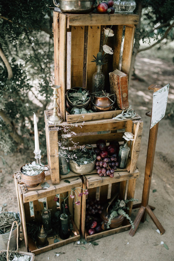 Crates filled with wine bottles, grapes, flowers and eucalyptus served as decor