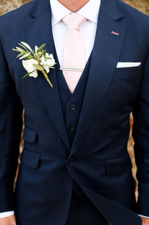 a navy suit with a blush tie and ivory flowers