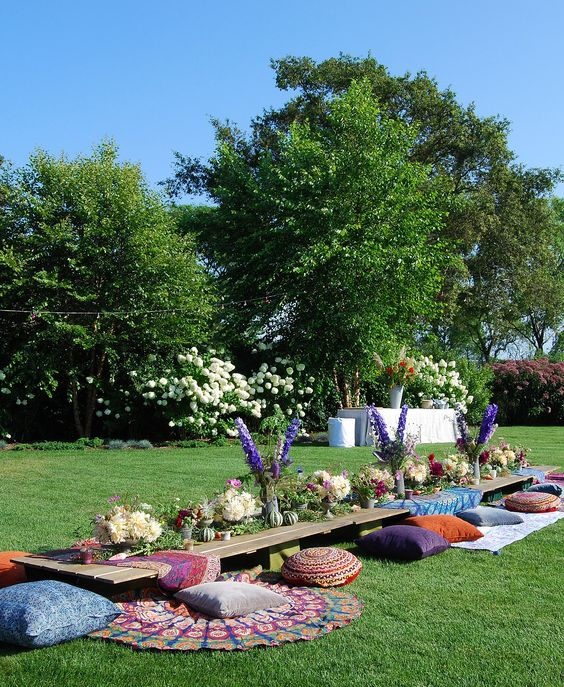 backyard boho picnic setting with colorful textiles and a lush table runner