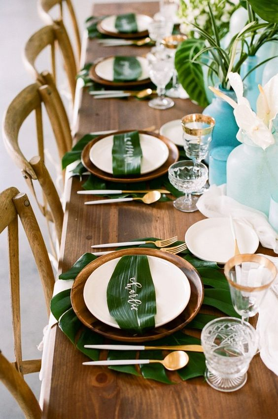 tropical tablescape with wood, calligraphy on leaves and gold