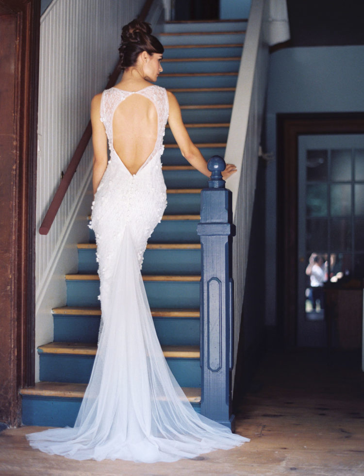 A back cutout and darling beaded detail, plus the flowing train make this gown stunning