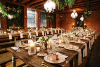 07 The reception was lit with candles and refined chandeliers, rustic wooden tables and benches looked contrasting with brick walls