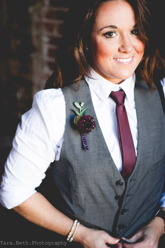 a grey vest, a white shirt, a burgundy tie and boutonniere