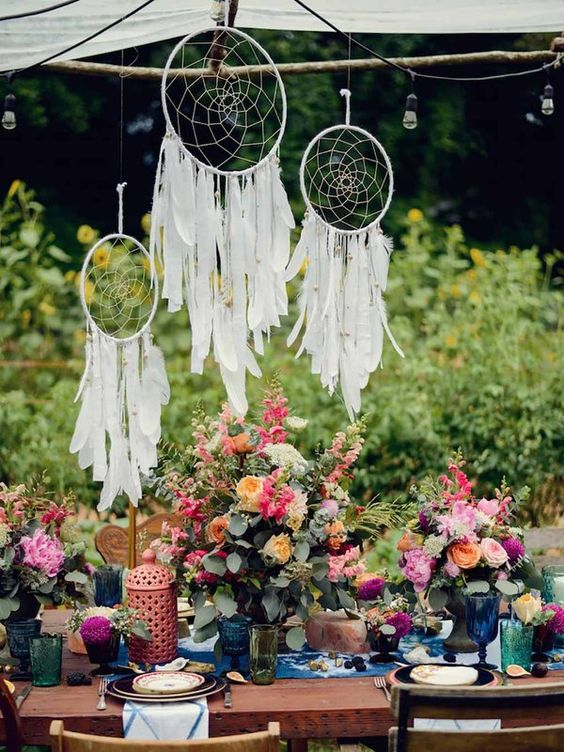 bold boho table setting with colorful florals and textiles, white dreamcatchers