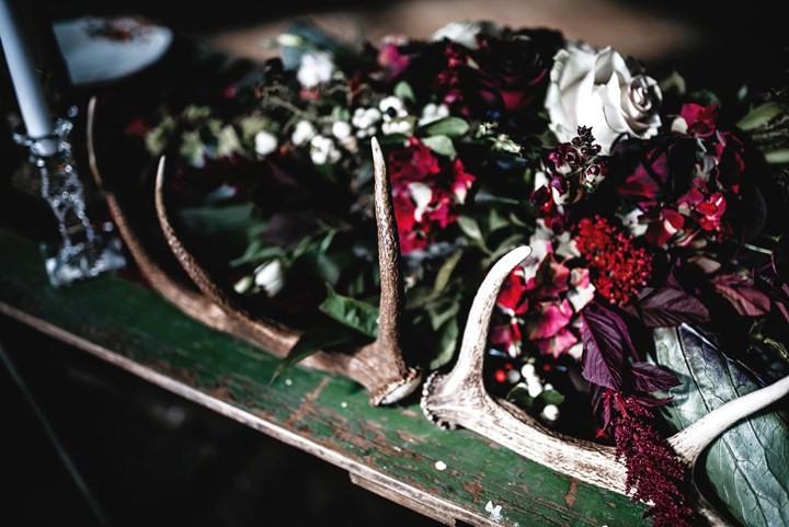 Antlers and moody florals are a sophisticated idea for dark color weddings