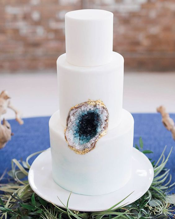 all-white cake with a blue geode insert and a gold rim