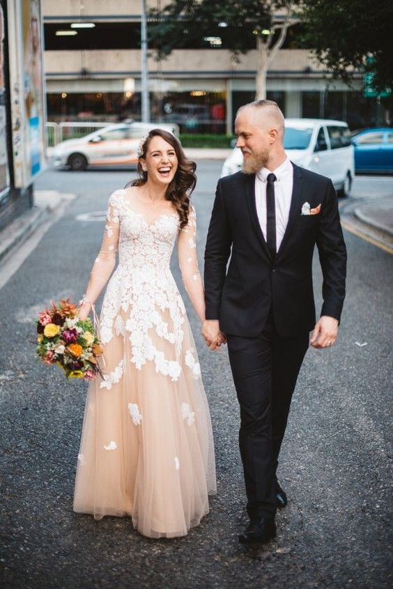 the groom in a black tuxedo with a thin tie, the bride in a blush wedding dress with white lace appliques