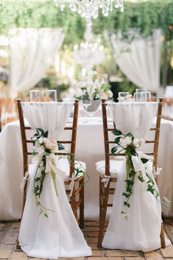 white fabric and blush flowers for decorating chairs
