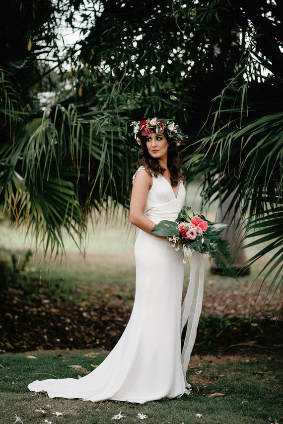 A bold pink bridal bouquet with palm leaves echoed with a lush floral crown in pink and red