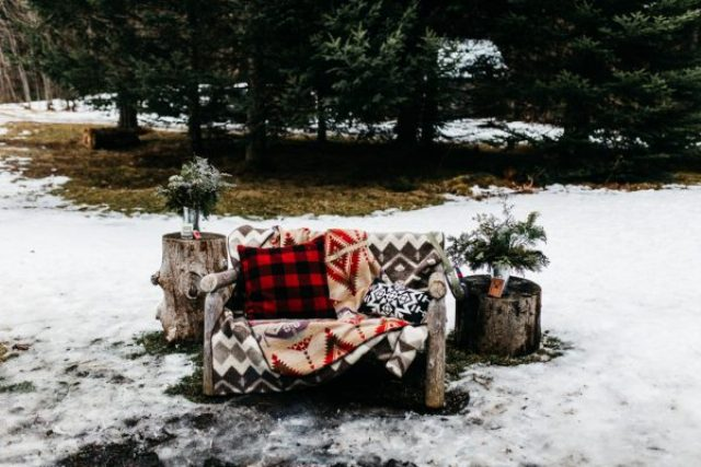 A rough wood bench was covered with blankets and pillows and looked very woodland-like