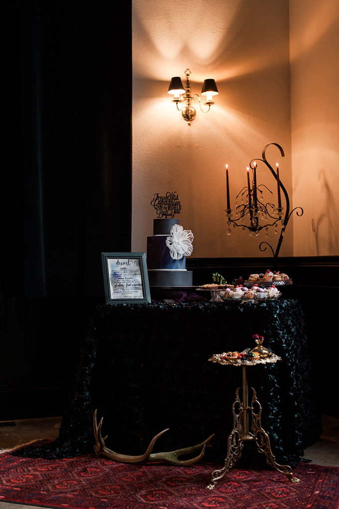 The dessert table was covered with black fabric and a dark cake and moody desserts continued the decor theme