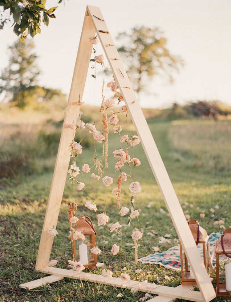 This is a wedding altar made of wooden beams and blush roses for a dreamy look