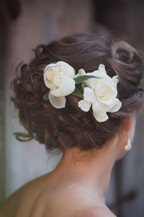 curled and braided updo with gardenia flowers