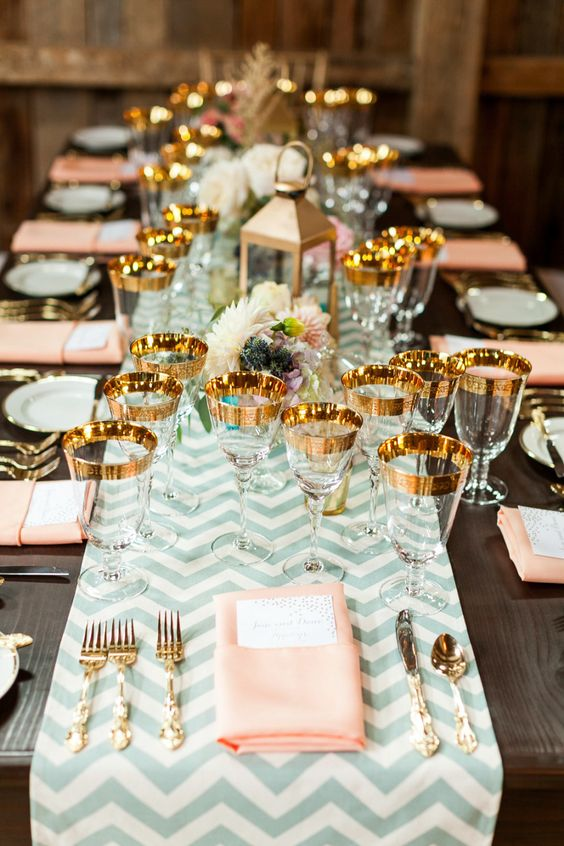 gold-rimmed glassware, blush napkins and mint chevron table runner
