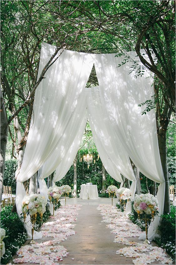 stunning garden aisle with airy fabrics, petals and flower topiaries