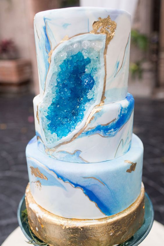 two trends in one   a bold blue marble wedding cake with geodes