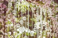 10 a wedding arch with cherry blossom and hanging crystals is a gorgeous idea for outdoors