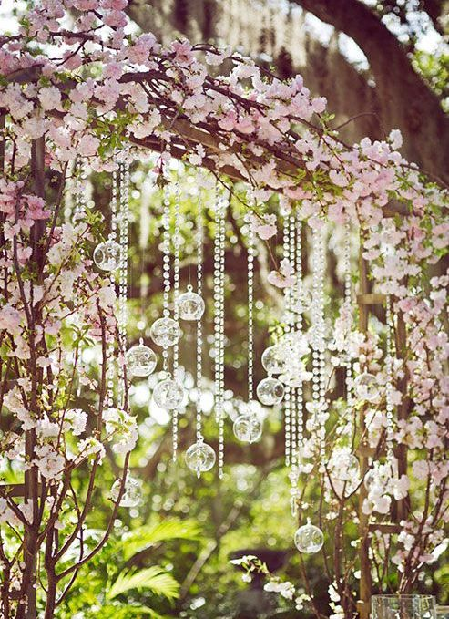 a wedding arch with cherry blossom and hanging crystals is a gorgeous idea for outdoors