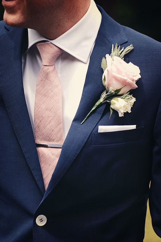 stylish navy suit, a blush rose boutonniere and tie
