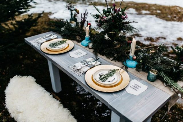 The sweetheart table was decorated with evergreen branches, leaves and candles